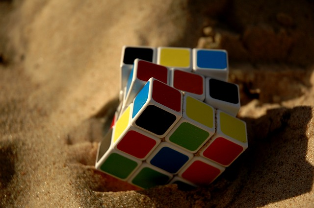 A Rubik cube on the sand, depicting challenge