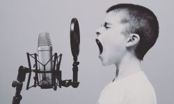 Picture of a boy and an old fashioned microphone