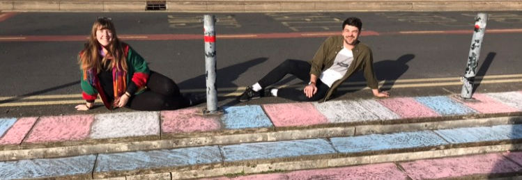 LGBTQ+ officers sitting on steps smiling