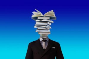A composite image of a man in a suit with a stack of books substituting their head.