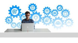 Image of person sitting at a computer surrounded by cogs and icons