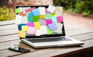Image of a laptop covered with post it notes