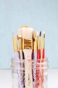 Image of a jar with paintbrushes of different shapes and sizes