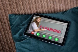 A tablet device with an image of an instructor pointing out the word 'e-learning'