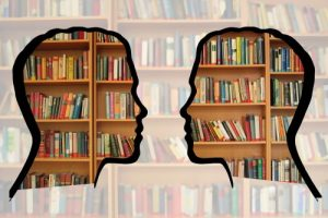 Composite image, two profile heads facing each other, overlaid in front of a bookshelf