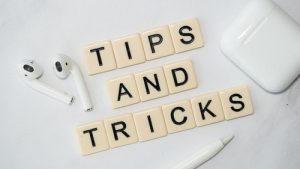 Using scrabble tiles, this image spells the words 'Tips and Tricks'