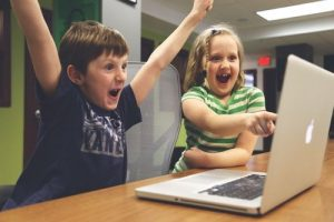 Two excited children looking very engaged by a laptop