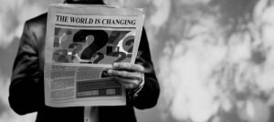 Image of a man holding a newspaper with a 'The World is Changing' headline